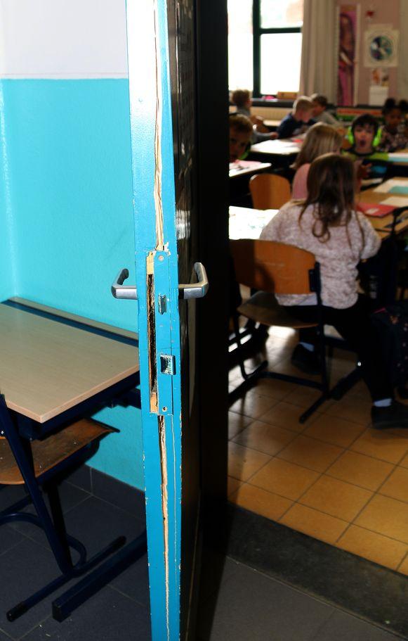 De schade aan de deur van het klaslokaal.
