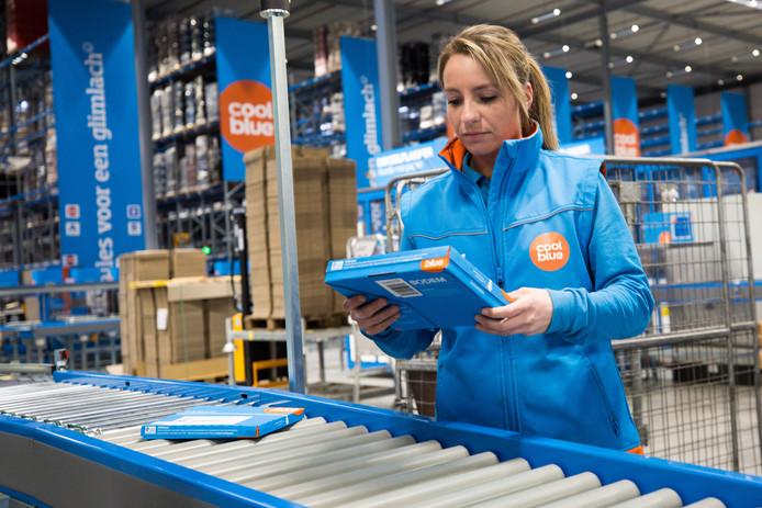 Een medewerkster van Coolblue bij de nieuwe pakketjesmachine in Tilburg, die minder lucht inpakt.