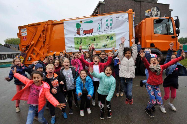 De leerlingen poseren fier bij hun tekening op de vuilniswagen.