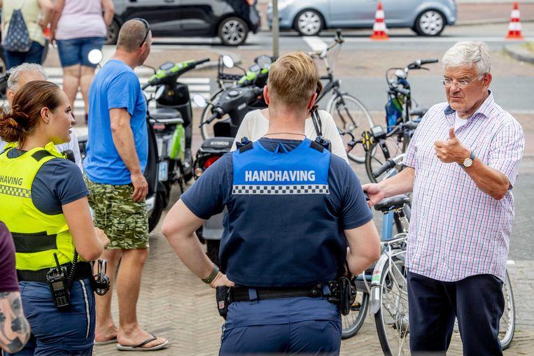 De Haagse burgemeester Jan van Zanen tijdens een gesprek met handhavers en verkeersregelaars over de knelpunten van Scheveningen. Beeld ANP
