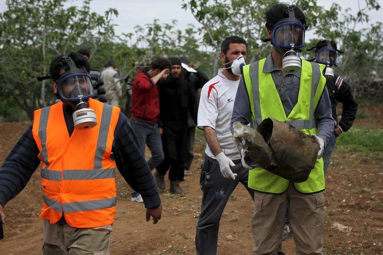 Syrische vrijwilligers met gasmaskers op dragen een vat waar vermoedelijk chloor in heeft gezeten. Beeld Reuters