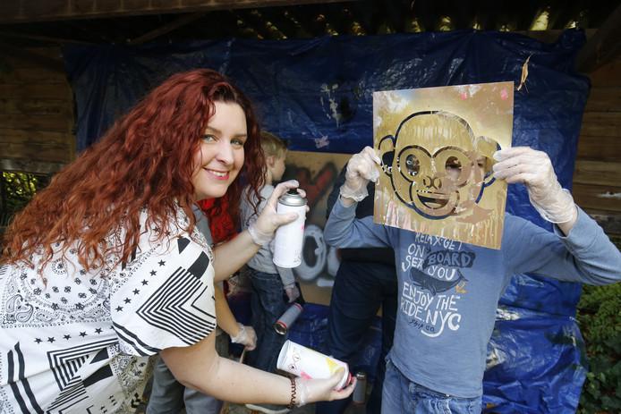 Organisator Melissa Naber gewapend met spuitbus om het sjabloon van een aap in te kleuren
