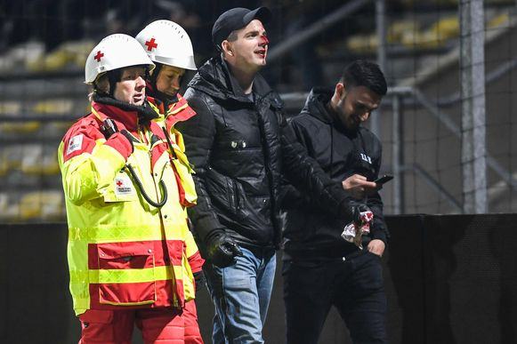 Een gewonde supporter van Lierse wordt afgevoerd.