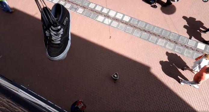 Jongens proberen met een magneet muntgeld uit het bakje van straatmuzikanten te vissen in Nijmegen.