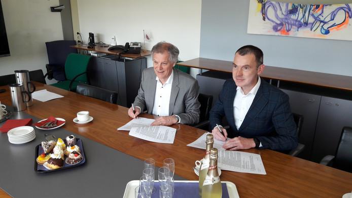 Wim van Harten (links) en wethouder Wijnte Hol zetten hun handtekening onder de plannen om in Elst een nieuwe poli-kliniek te bouwen.