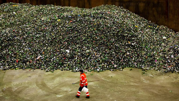 Een medewerker van een glasrecyclingbedrijf verwerkt de enorme hoeveelheid flessen na de feestdagen. Beeld anp