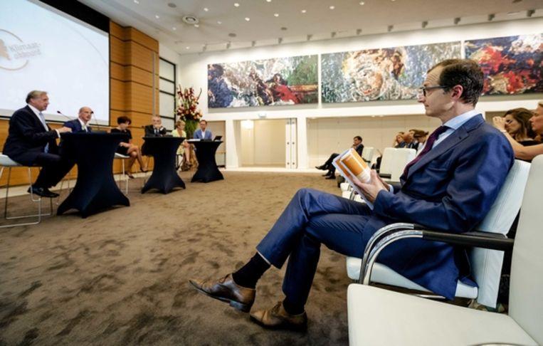 Minister Wiebes bekijkt het rapport met de hoofdlijnen van het Klimaatakkoord dat hij kreeg aangeboden door voorzitter Ed Nijpels. Beeld ANP