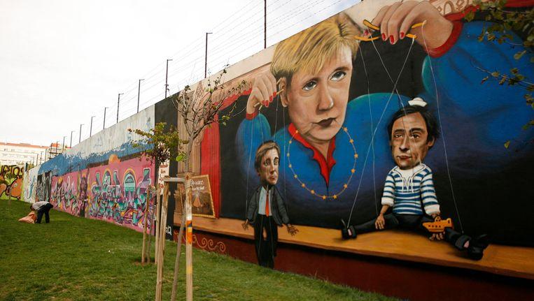 Een protest tegen de macht van Angela Merkel in Lissabon. Beeld reuters