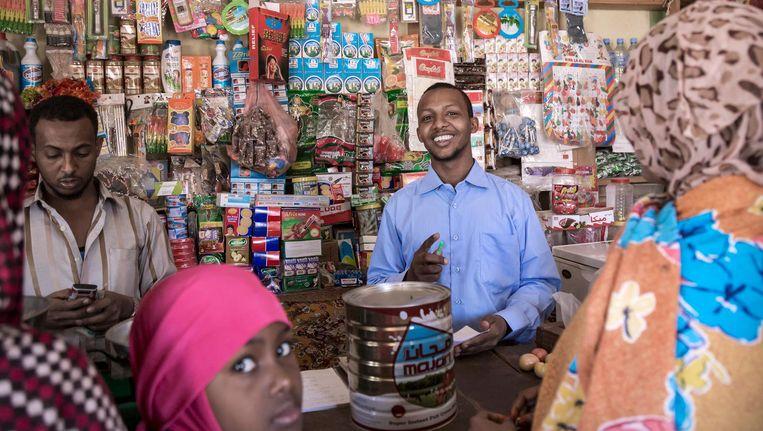 Ahmed Salebaan Awil (links) in zijn kruidenierswinkel in Burao. Zijn neef in Nederland stuurt geregeld geld waarmee hij inkopen kan doen voor zijn door droogte getroffen familie. Beeld Sven Torfinn