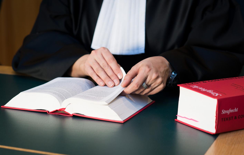 2014-03-05 00:00:00 ILLUSTRATIE - Een rechter bekijkt het wetboek in de rechtzaal. ANP XTRA ROOS KOOLE