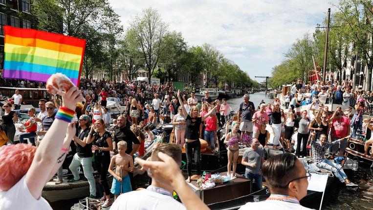 Feestvierende toeschouwers tijdens de botenparade in de grachten. Beeld anp