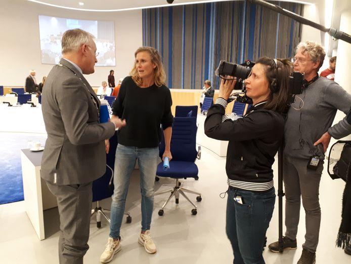 Presentatrice Sophie Hilbrand probeert tevergeefs een vraaggesprek te regelen met burgemeester Arjen Gerritsen, na afloop van een raadsvergadering.