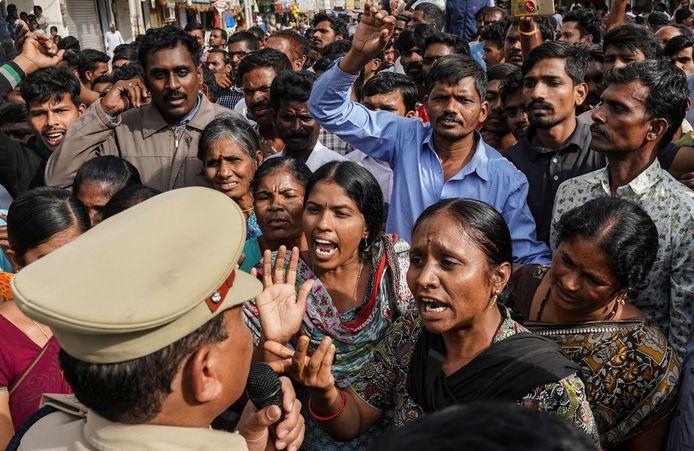 Boze demonstranten in discussie met een politieman die het kantoor bewaakt waar de vier mannen opgesloten zitten.