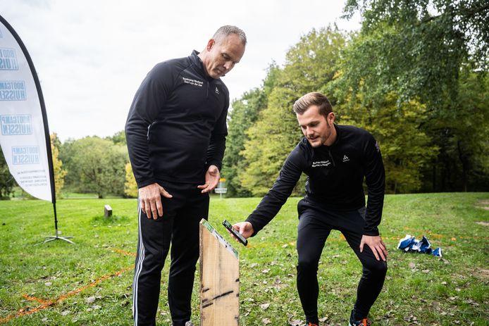 Marwan van Heugten scant, onder toeziend oog van compagnon Evert van der Zee, de QR-code van een van de bootcampstations in Park Immerloo.