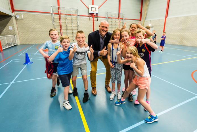 Initiatiefnemer Henny van de Heijden tussen kinderen die in De Vierstee sporten.