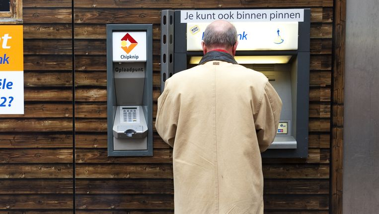 Een gepensioneerde man bij de pinautomaat. Beeld anp