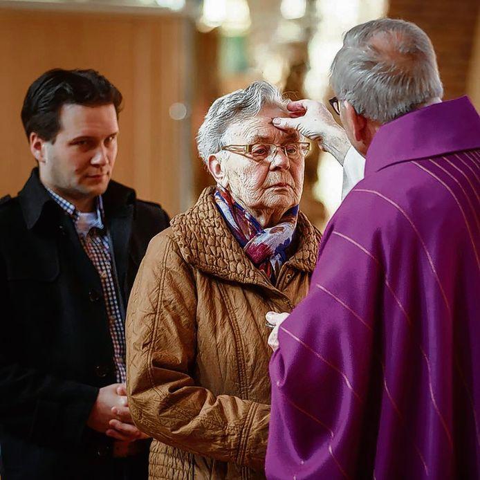 Archieffoto waarbij kerkgangers op Aswoensdag (de woensdag na Carnaval waarop de Vastentijd begint) het askruisje ontvangen van pastor Peter de Rooij. Ook die handeling zou op dit moment niet mogelijk zijn.