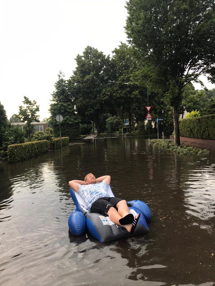 Jari uit Goirle maakt van de situatie gebruik door op het water te dobberen op de Van Malsenstraat in Goirle.