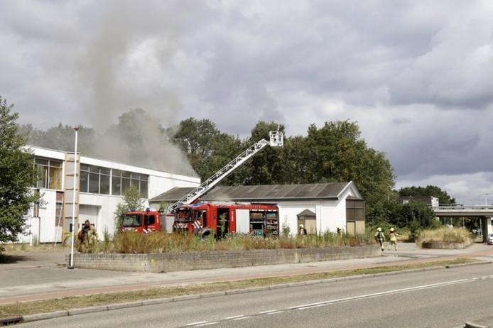 De brandweer aan het werk bij de brand in een voormalige melkfabriek in Leunen.
