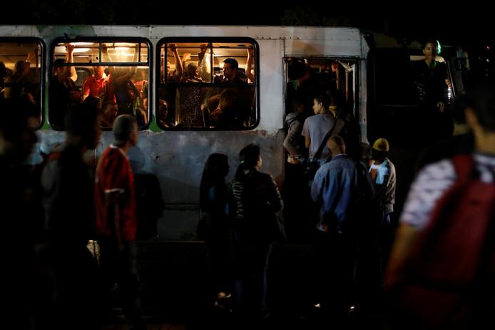 In het donker nemen mensen de bus tijdens de stroomuitval in Venezuela.
