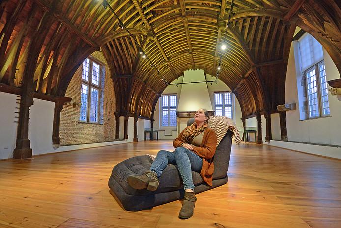 Wil van Velthoven, weekendmanager bij het Stadhuismuseum, bekijkt de houten kapconstructie in de bovenzaal vanuit een relaxstoel.