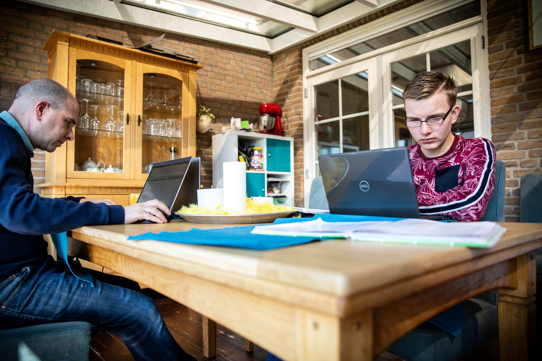 Laurens Stoop volgt thuis onderwijs. Links op de foto zijn vader Ruud, die ook thuiswerkt.