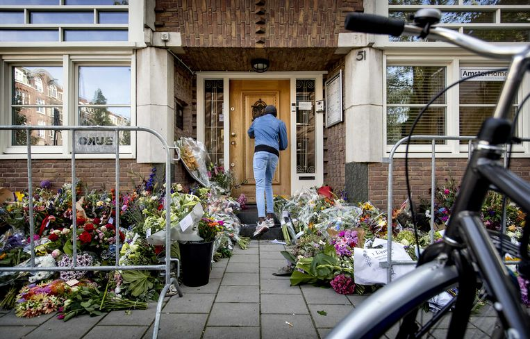 Mensen leggen bloemen bij het kantoor van de doodgeschoten advocaat Derk Wiersum. Beeld ANP
