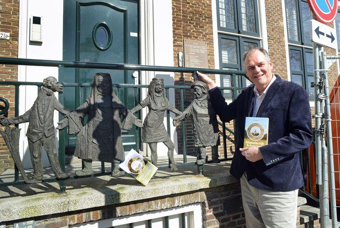 Auteur Henk Dalebout met zijn boek bij het door Ad Braat gemaakte bronzen reliëf van de Franciscanessen in de voormalige Corneliastichting in Zierikzee.