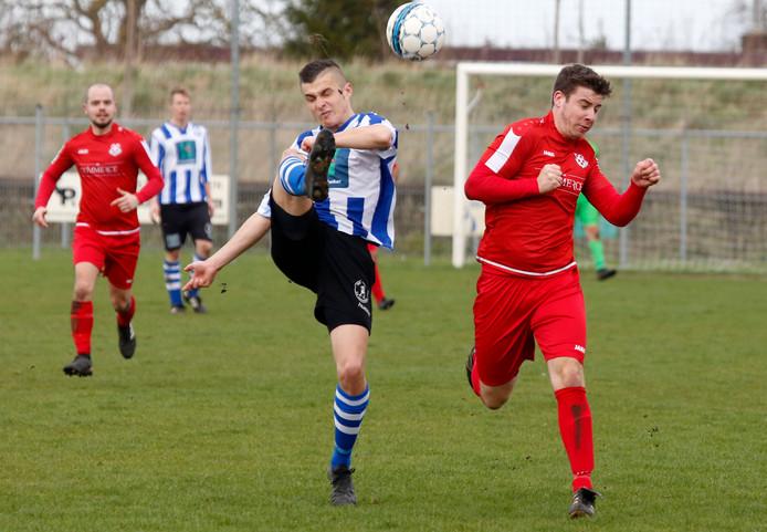 IJzendijke-verdediger Max Calon (links) werkt de bal weg voordat Biervliet-aanvaller Mark de Feijter erbij kan.