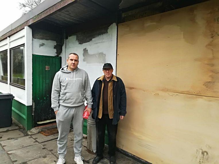 Voorzitter Tom Van Gestel en penningmeester Theo Rens bij de beschadigde deur. Voor de beschadigde toiletten is een houten plaat geslagen.