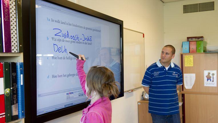 Een leerling schrijft op een digitaal schoolbord. Leraar kijkt toe. Beeld anp