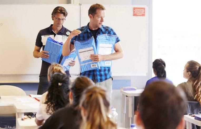 Een leraar deelt eindexamens uit in een klaslokaal. Beeld anp