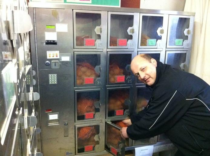 Rien Hissink demonstreert de werking van zijn aardappelautomaat. Foto: Rick Aalbers/De Gelderlander