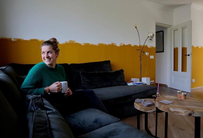 """Irene van Eenennaam voor haar half geschilderde muur. ,,Laatst dacht iemand dat de muur nog in de voorstrijk zat."""""""