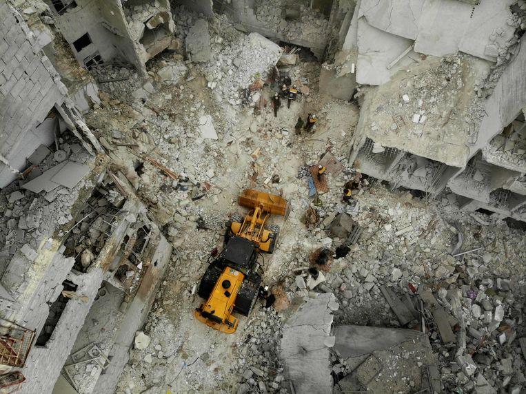 Reddingwerkers proberen woensdag met een graafmachine slachtoffers onder een ingestorte flat vandaan te halen in de rebellenstad Ariha, na een bombardement van Syrische regeringstroepen.  Beeld AFP