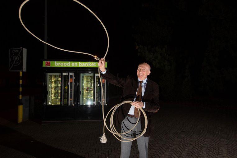 Burgemeester Dirk De Vis, met zijn lasso, voor de broodautomaat waar een dronken man hem op de zenuwen werkte.