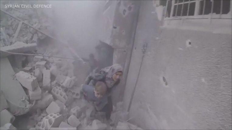 Kinderen en hun moeders vluchten uit een gebouw na een zoveelste bombardement in Oost-Ghouta.