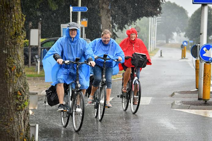 Fietsers in de eerste grote regenbui na lange droogte. Drentse toeristen uit Smilde op fietsvakantie in Twente.