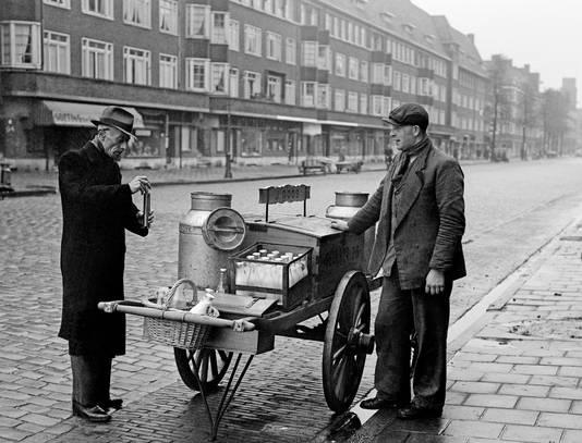 Een ambtenaar van de Keuringsdienst van Waren controleert een melkboer in Amsterdam in 1946