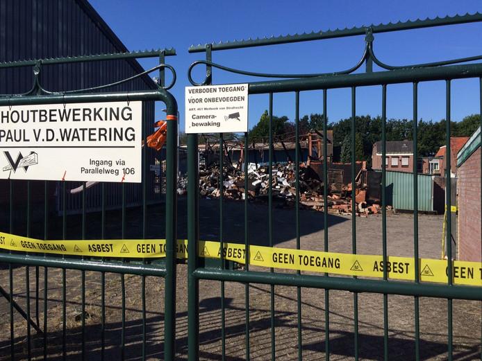 De restanten van de loods de dag na de brand. Het terrein is afgesloten omdat bij de brand asbest is vrijgekomen.