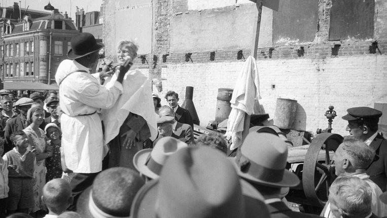 'Mister Menthol' Joseph Sylvester demonstreert tandpasta op het Waterlooplein. Beeld Stadsarchief