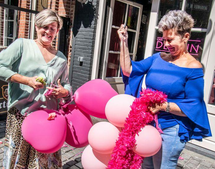 """Jolanda Wijnans (links) en Bernadette van den Broek prikken de roze ballonnen lek. ,,De afgelopen vier kermisdagen hebben meer stress opgeleverd dan de elf weken coronasluiting."""""""