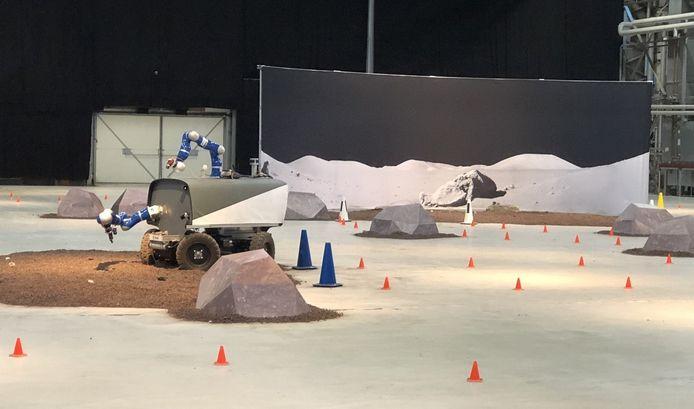 De robotauto rijdt rond in de hangaar in Valkenburg, terwijl hij door een astronaut wordt bestuurd in het ruimtestation ISS