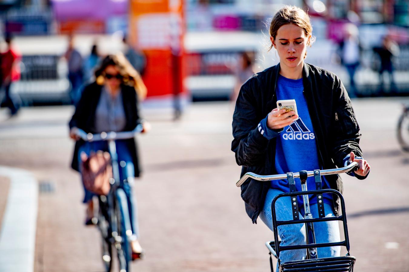 Een vrouw appt op de fiets in Amsterdam.
