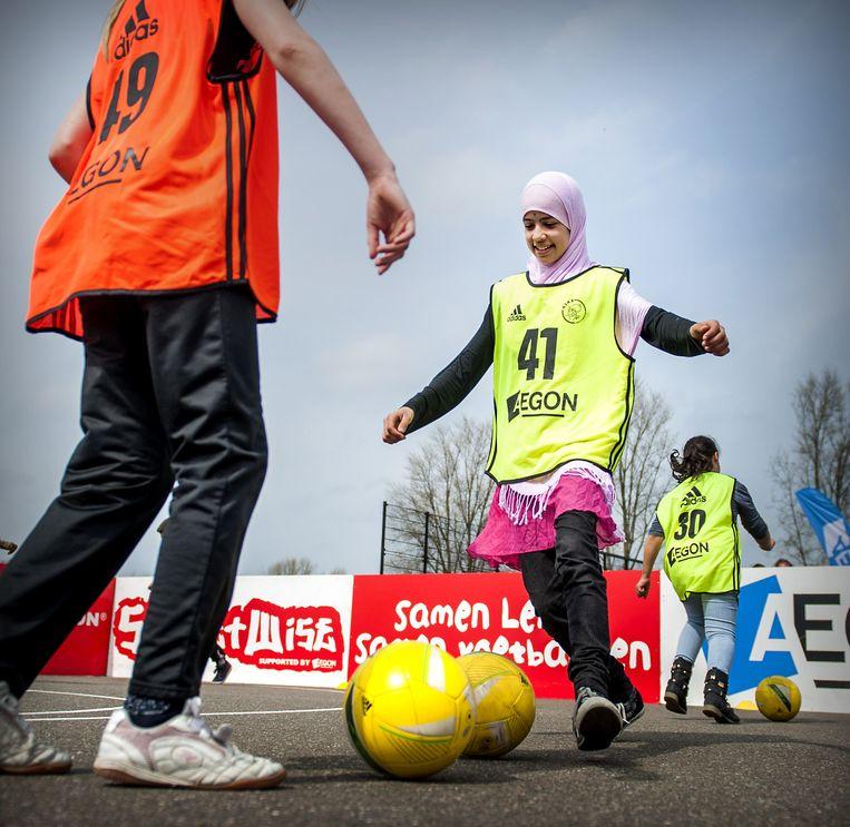 Kinderen voetballen tijdens de Ajax StreetWise clinic op het Cruyff Court Seedorfplein, 2013. Beeld ANP