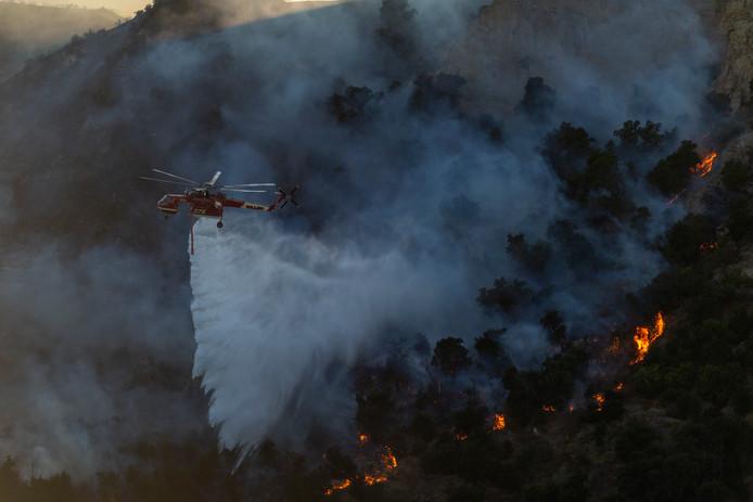 Een helikopter vliegt over de Saddleridge branden dichtbij Newhall, Californië.