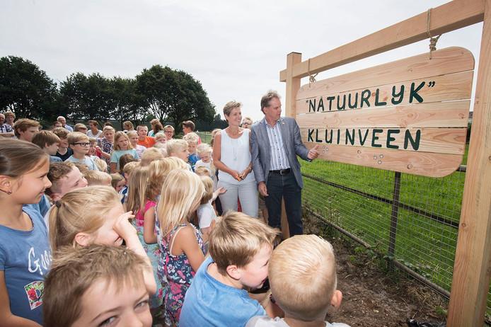 Schoolkinderen kijken toe als hun speelplaats wordt geopend door de wethouder.