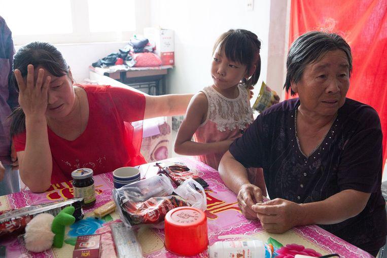 Liu Runfeng (l) met dochter in Huaziucun. Runfengs neef, brandweerman Zhiquang, wordt vermist in Tianjin. Beeld WassinkLundgren