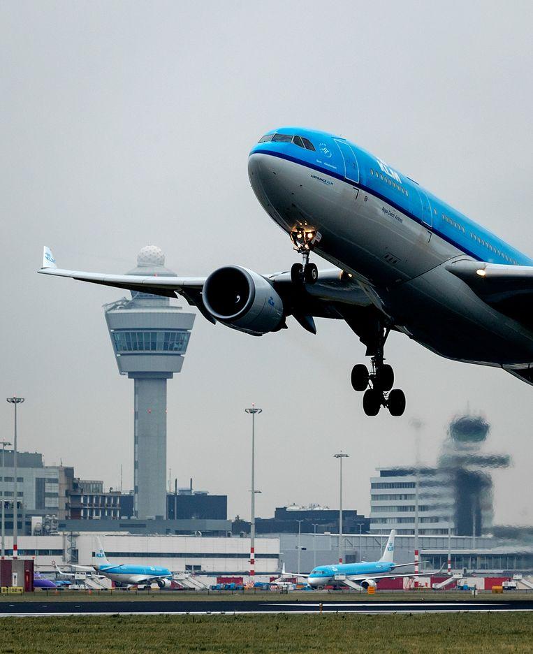 Een vliegtuig van KLM stijgt op van een landingsbaan van Schiphol. Het ministerie van Infrastructuur en Waterstaat onderzoekt hoe de luchthaven haar start- en landingsbanen kan uitbreiden. Beeld ANP XTRA