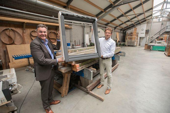 Arie van Liempd (links) van het gelijknamige sloopbedrijf uit Sint-Oedenrode en Ronald Bal van Velux bij het dakraam bestaande uit sloophout uit Rotterdamse woningen. FOTO KEES MARTENS/FOTOMEULENHOF